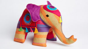 A hand stitched and hand loomed bright coloured soft elephant.